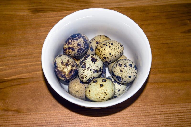 Ovos de codorniz em uma placa branca pequena em um fundo de madeira, estando na tabela foto de stock