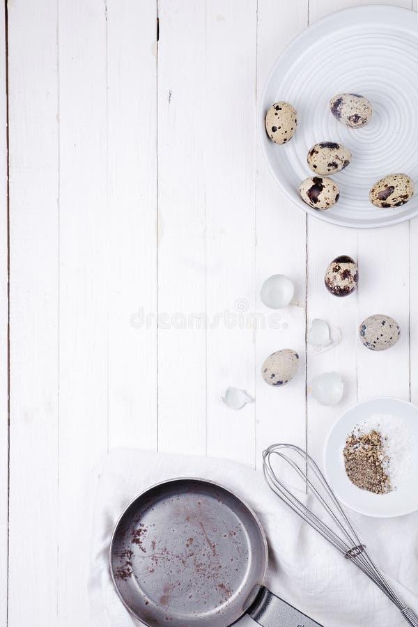 Ovos de codorniz em uma placa, em um escudo, em um batedor de ovos para bater e em uma frigideira em um fundo de madeira branco V foto de stock