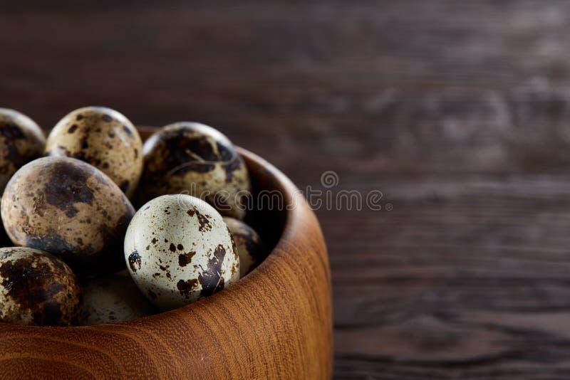 Ovos de codorniz frescos em uma bacia de madeira em um fundo de madeira escuro, vista superior, close-up foto de stock royalty free