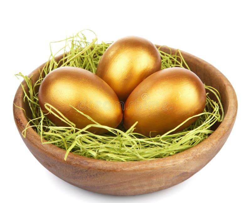 Ovos de easter dourados na bacia isolada imagem de stock