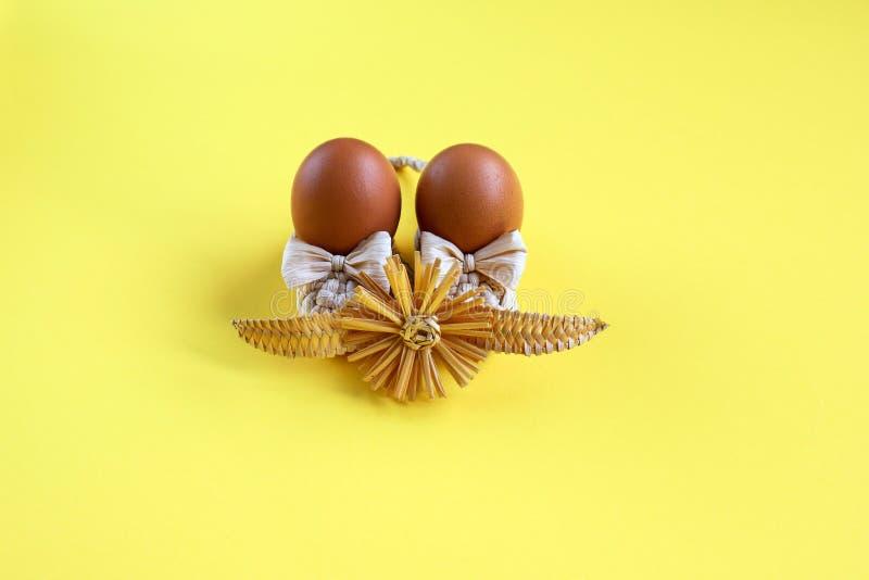 Ovos de galinha orgânicos marrons com palha, com flor em fundo amarelo, feriados na Páscoa imagem de stock royalty free