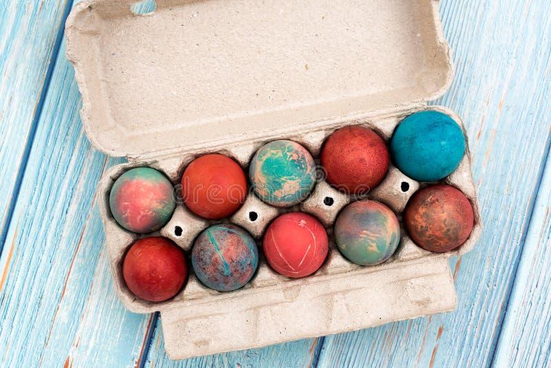 Ovos de Páscoa coloridos em caixa de ovos de cartão numa mesa de madeira azul fotografia de stock royalty free