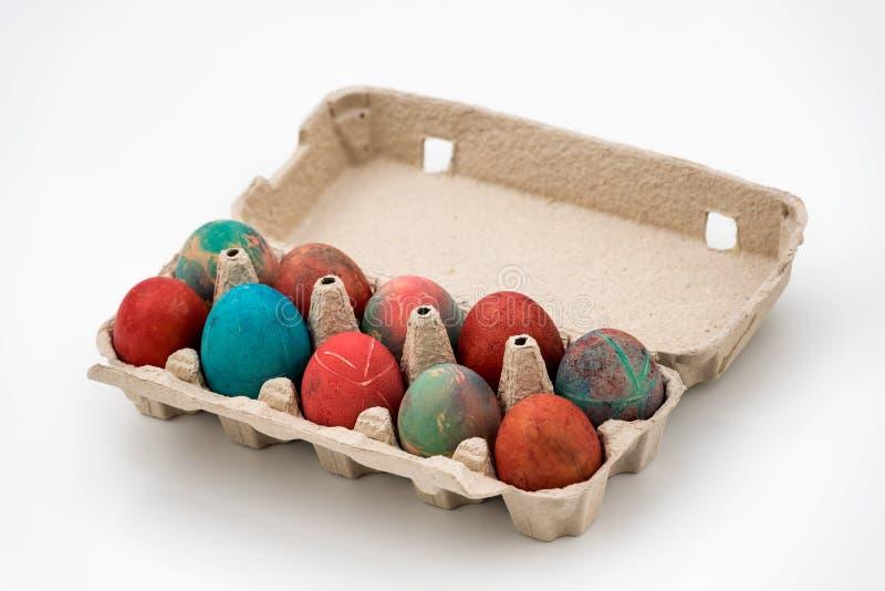 Ovos de Páscoa coloridos na caixa de ovos de papelão em fundo branco fotos de stock royalty free