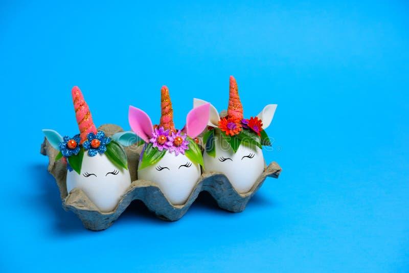 Ovos de unicórnio da Páscoa caindo em um fundo azul com espaço de cópia fotografia de stock royalty free