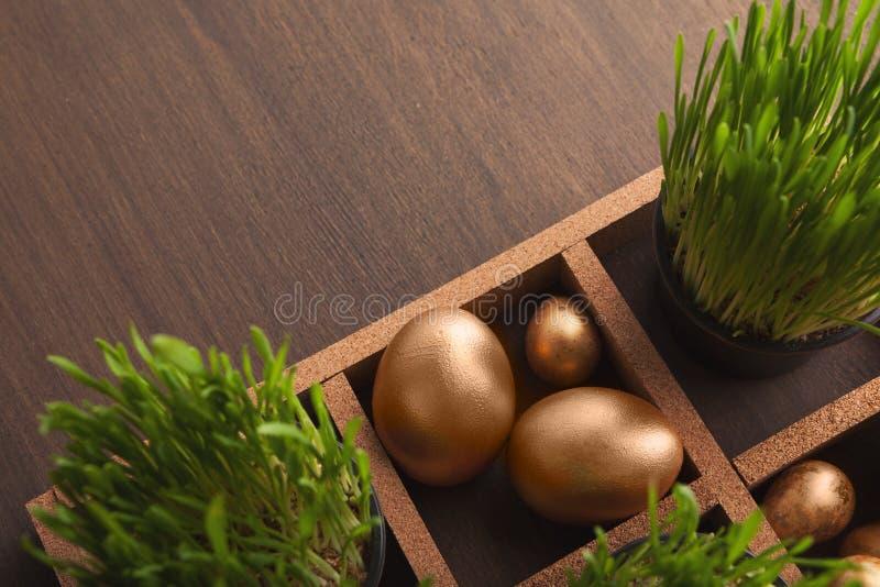 Ovos dourados e grama verde na tabela marrom imagem de stock royalty free