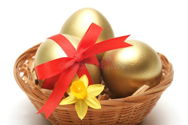 Ovos dourados na cesta imagens de stock royalty free