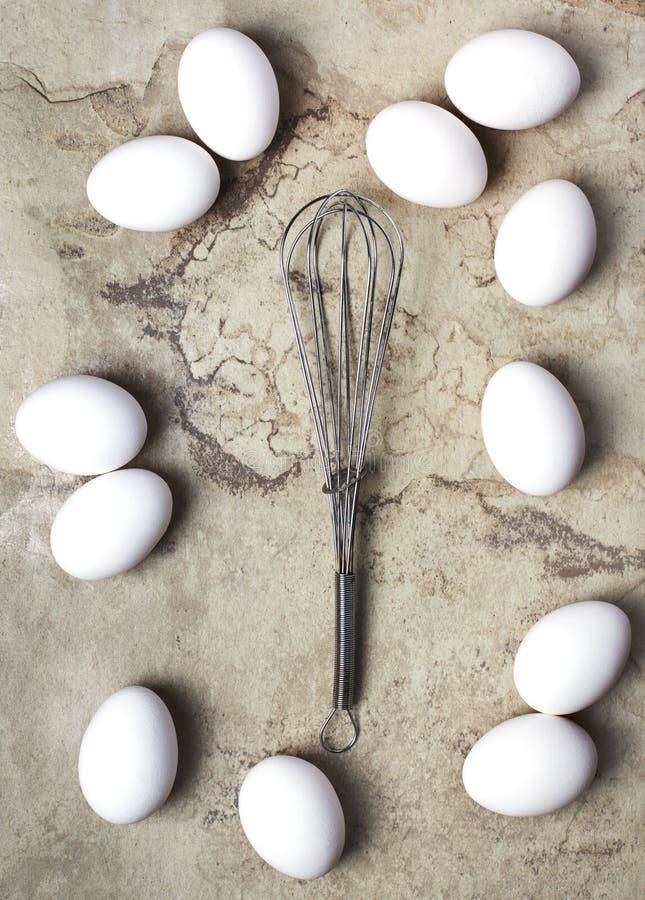 Ovos e batedor de ovos crus da galinha no fundo de pedra, fotos de stock