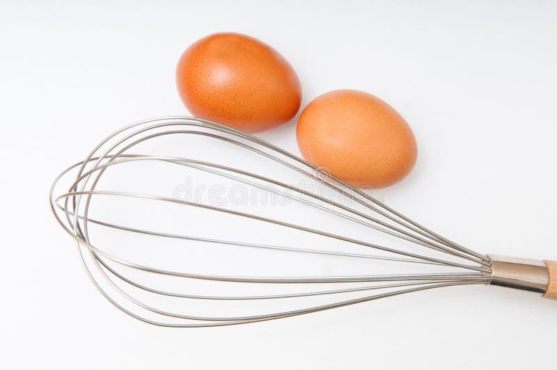 Ovos e batedor de ovos fotografia de stock royalty free