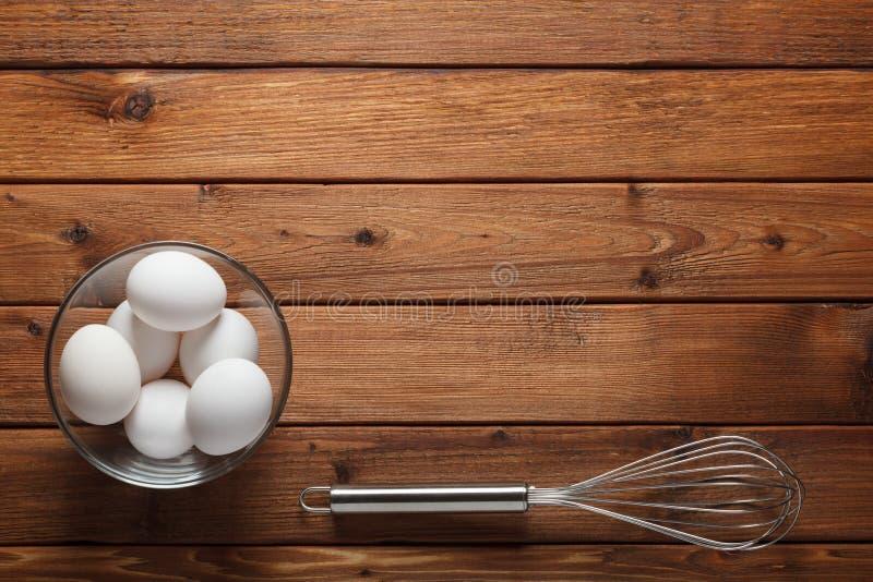 Ovos e batedor de ovos do fio na tabela rústica fotos de stock