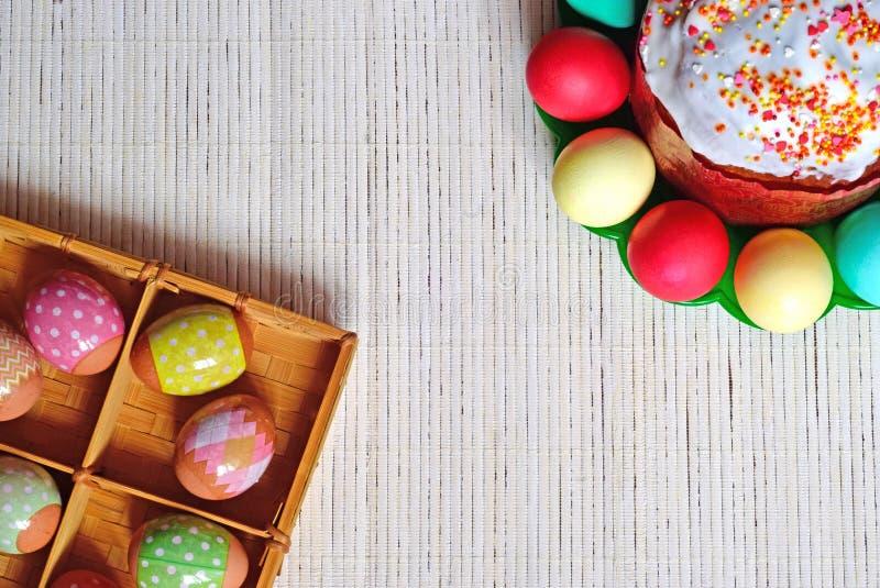 Ovos e bolo de Easter Ovos em uma cesta e em uma placa imagem de stock