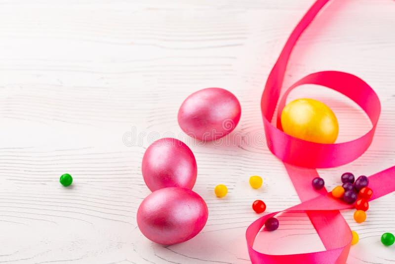 Ovos e doces coloridos da galinha em um fundo de madeira branco O conceito das felicita??es na P?scoa Close-up imagens de stock royalty free