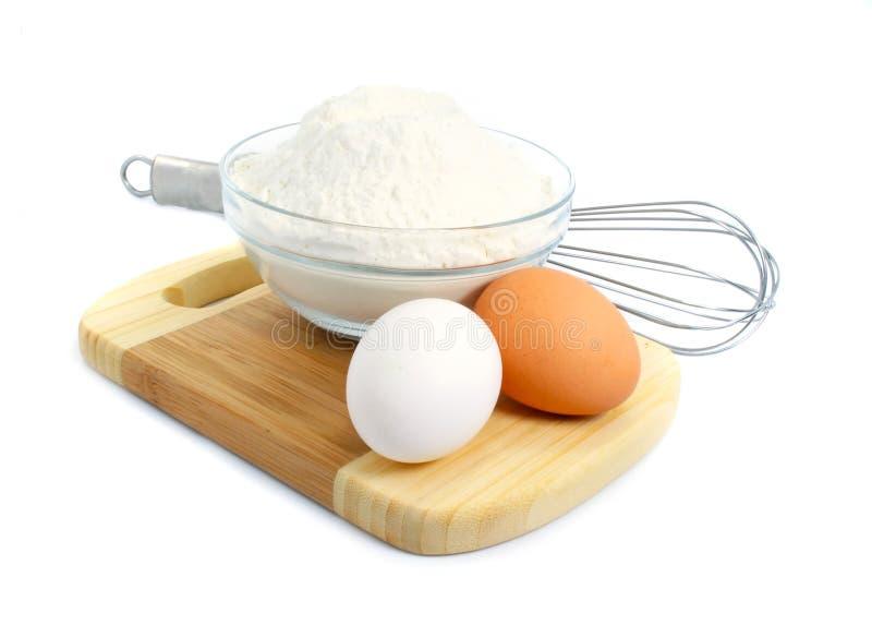 Ovos e ingredientes da farinha para a preparação da massa de pão fotografia de stock