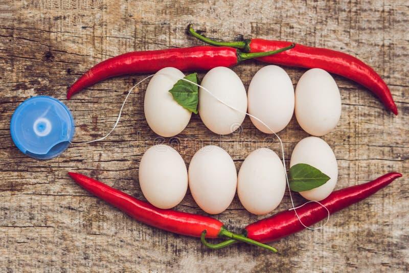 Ovos e pimentas vermelhas sob a forma de uma boca com dentes As folhas são coladas aos dentes e ao fio dental Limpeza sua fotos de stock