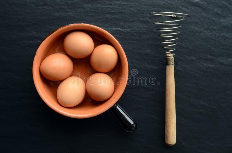 Ovos em uma bacia com eggbeater imagens de stock