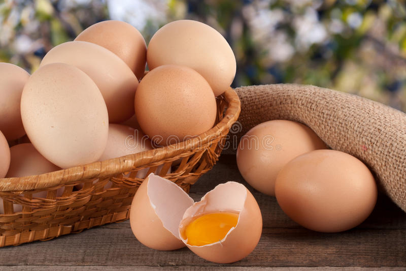 ovos em uma cesta de vime em uma placa de madeira com os vagabundos borrados do jardim fotografia de stock