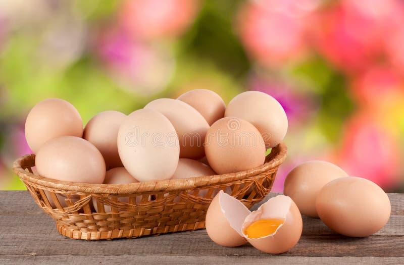 Ovos em uma cesta de vime em uma placa de madeira com fundo borrado do jardim imagem de stock