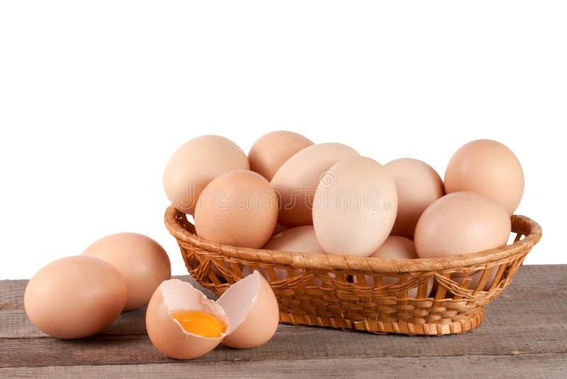 Ovos em uma tabela de madeira em uma cesta de vime em um fundo branco fotografia de stock royalty free