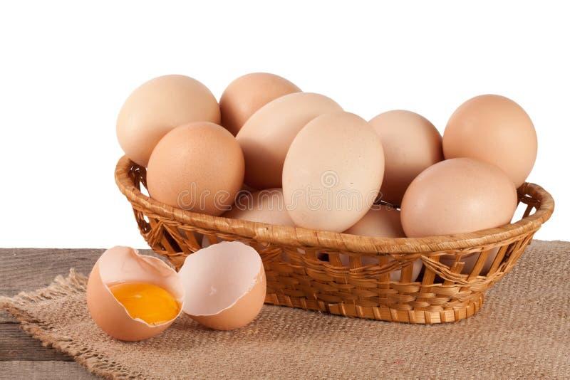 Ovos em uma tabela de madeira em uma cesta de vime em um fundo branco imagem de stock