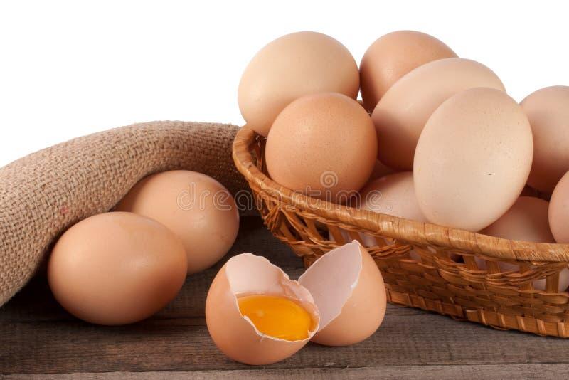 Ovos em uma tabela de madeira em uma cesta de vime em um fundo branco fotografia de stock