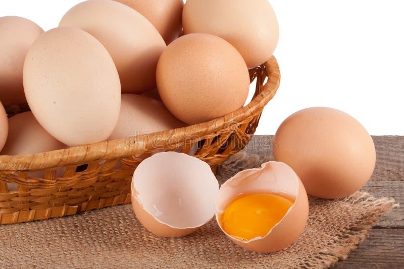 Ovos em uma tabela de madeira em uma cesta de vime em um fundo branco fotos de stock