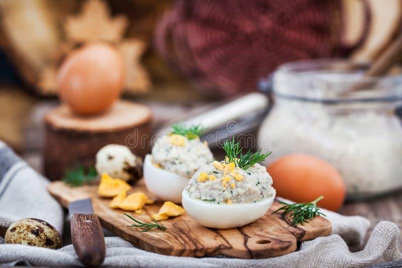 Ovos enchidos com pasta cremosa dos arenques no backgroun rústico de madeira imagem de stock