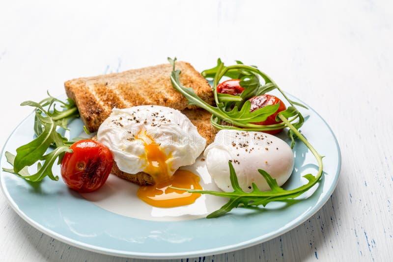 Ovos escalfados nos brindes Wholegrain do pão fotos de stock royalty free