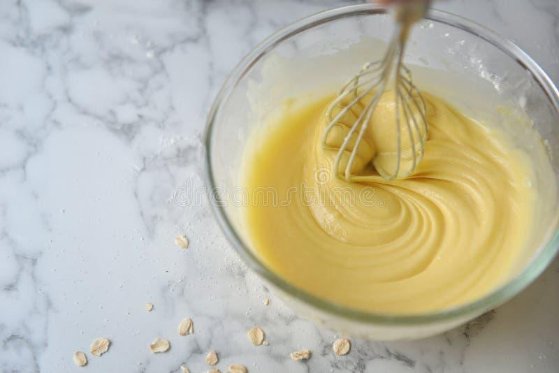 Ovos, farinha e leite de mistura na bacia com o batedor de ovos de prata do fio Conceito de cozinhar ingredientes e m?todo no fun fotos de stock royalty free