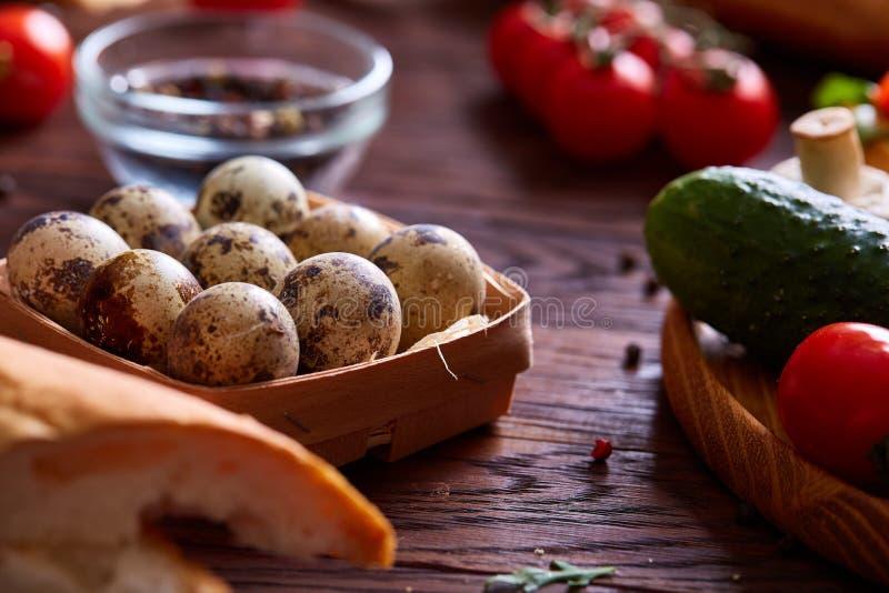 Ovos frescos de uma codorniz com verdes e de vegetais na tabela de madeira, foco seletivo, close-up fotografia de stock