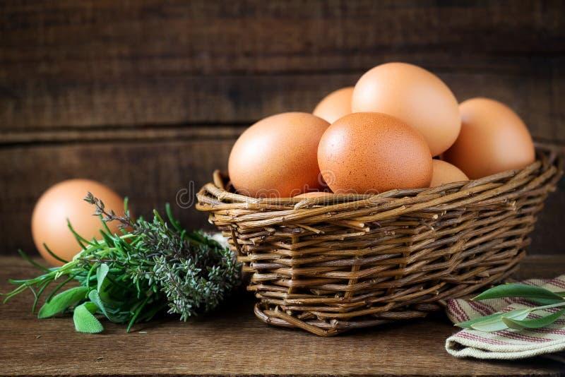 Ovos frescos em uma cesta do salgueiro com ervas aromáticas foto de stock royalty free
