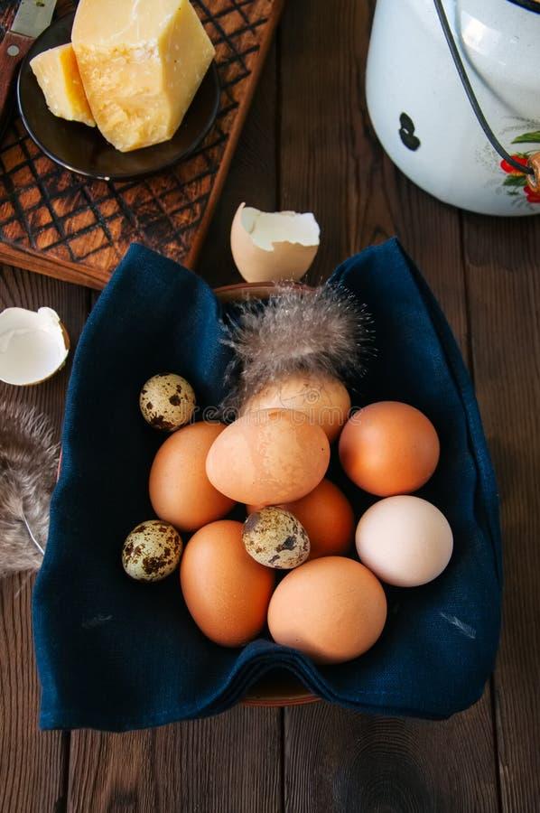 Ovos frescos em uma placa, leite em uma lata, queijo parmesão em um woode fotos de stock royalty free