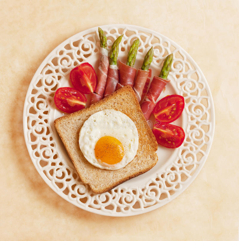 Ovos fritados no brinde, nos espargos e nos tomates fotos de stock royalty free