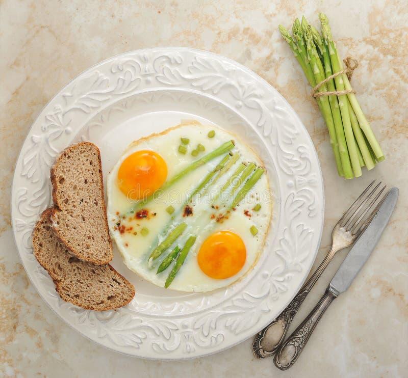 Ovos fritos com aspargo em uma placa - café da manhã saudável imagens de stock royalty free