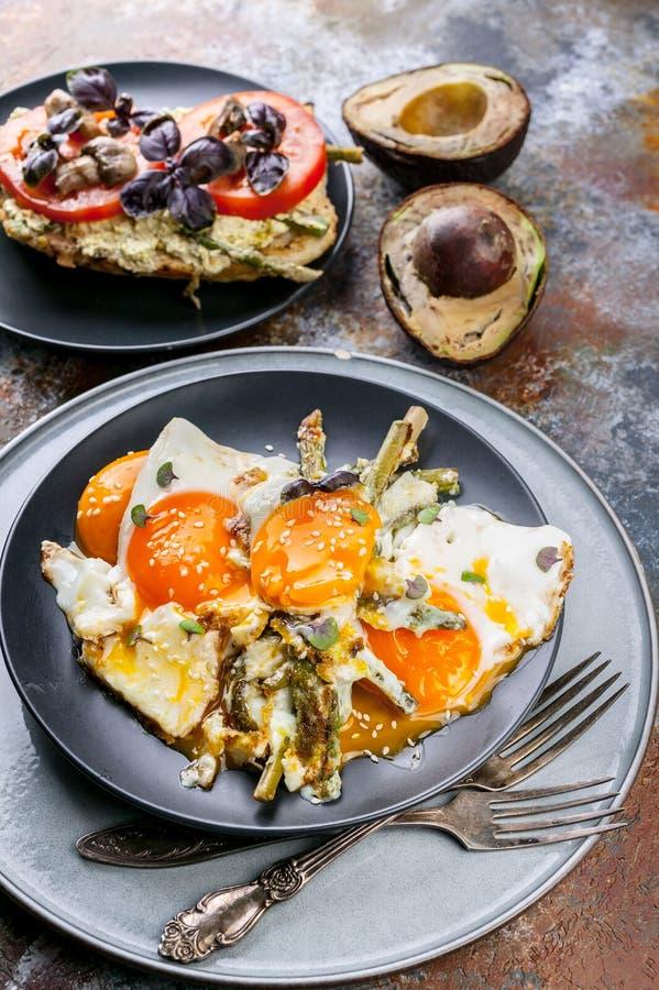 Ovos fritos com aspargo, sandu?che com pesto, tomates e cogumelos, abacate maduro Pequeno almo?o saboroso fotos de stock