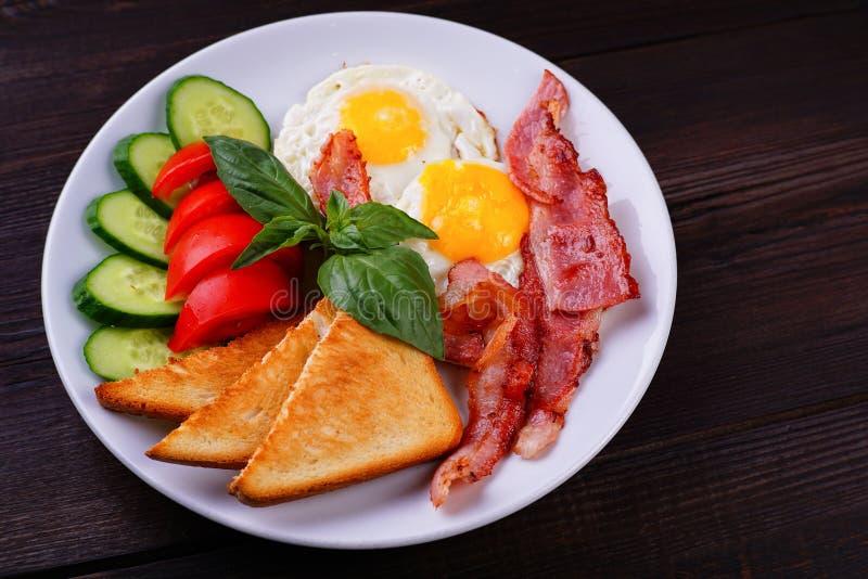 Ovos fritos com bacon, brindes e os legumes frescos foto de stock royalty free