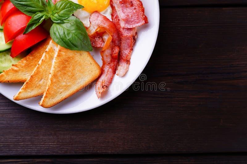 Ovos fritos com bacon, brindes e os legumes frescos imagem de stock