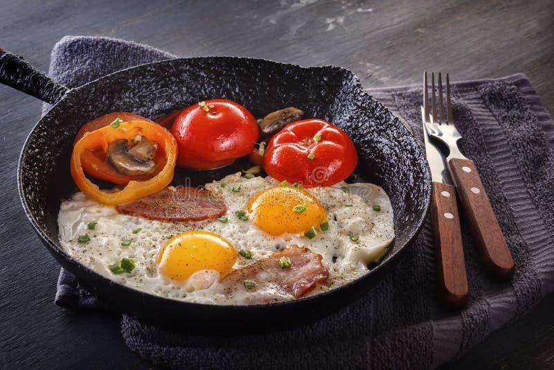 Ovos fritos com bacon e tomates em uma bandeja e em uma cutelaria velhas do ferro fundido em uma tabela cinzenta foto de stock