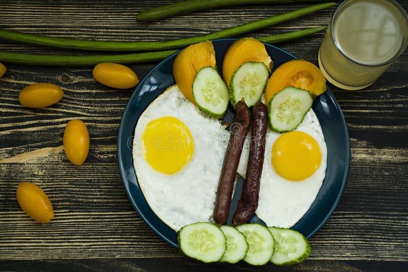 Ovos fritos e salsicha em uma placa azul da porcelana foto de stock
