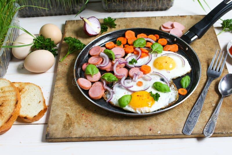 Ovos fritos em uma frigideira com vegetais fotografia de stock