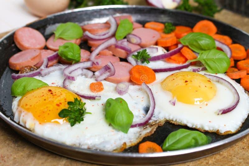 Ovos fritos em uma frigideira com vegetais imagens de stock