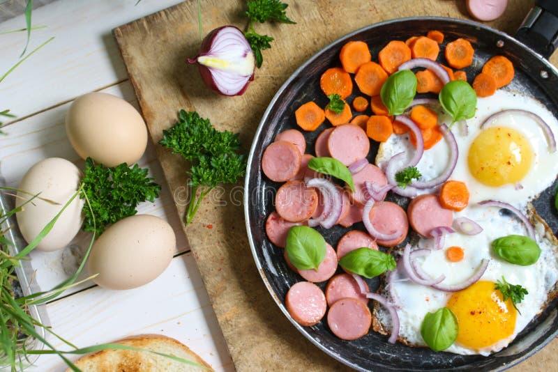 Ovos fritos em uma frigideira com vegetais fotos de stock royalty free