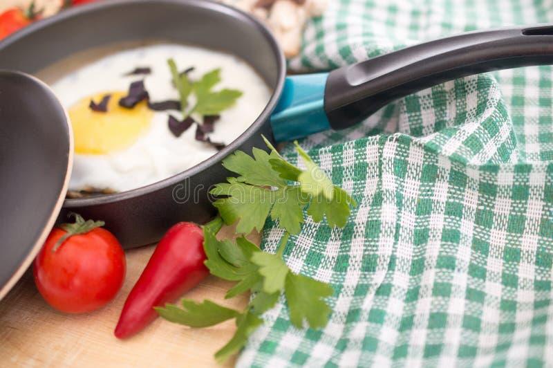 Ovos fritos em uma frigideira com verdes, tomates e pimento foto de stock royalty free