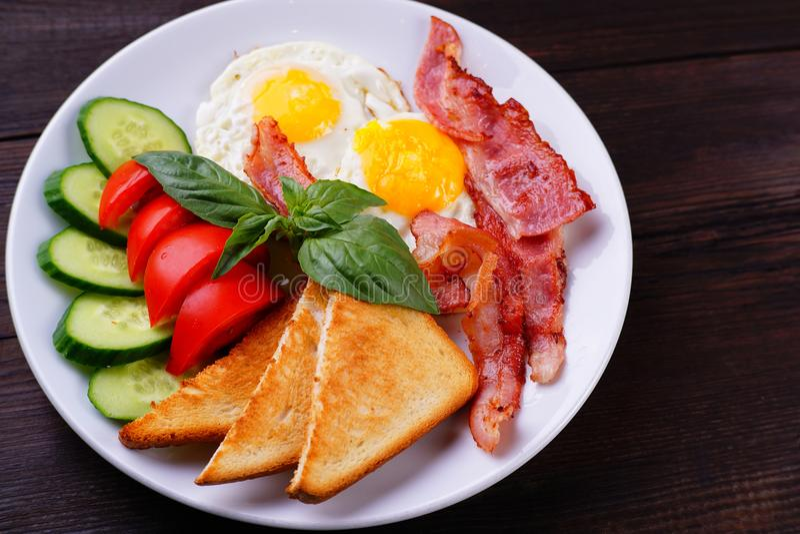 Ovos fritos europeus do café da manhã com bacon foto de stock royalty free