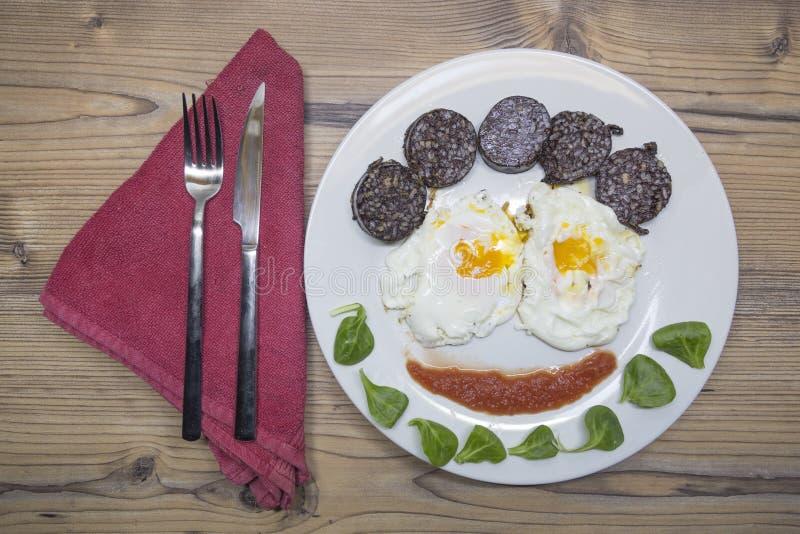 Ovos fritos na placa branca que forma uma cara imagens de stock royalty free