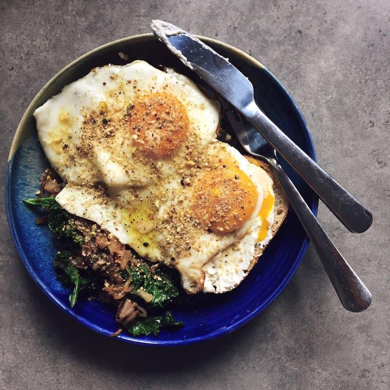 Ovos fritos sobre da couve e cebolas sautéed: café da manhã caseiro imagens de stock