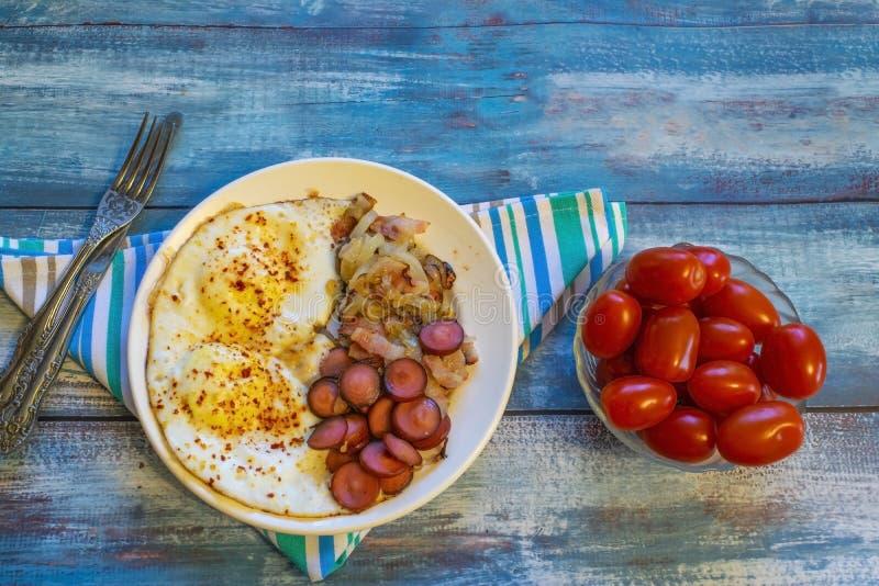 Ovos mexidos com bacon, cebola e salsicha imagem de stock royalty free