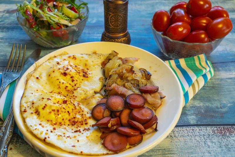 Ovos mexidos com bacon, cebola e salsicha fotografia de stock royalty free