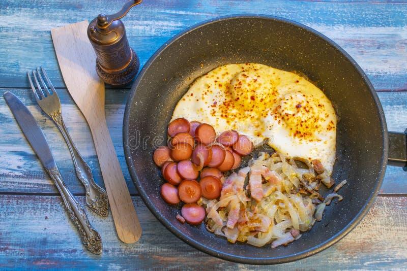 Ovos mexidos com bacon, cebola e salsicha imagens de stock royalty free