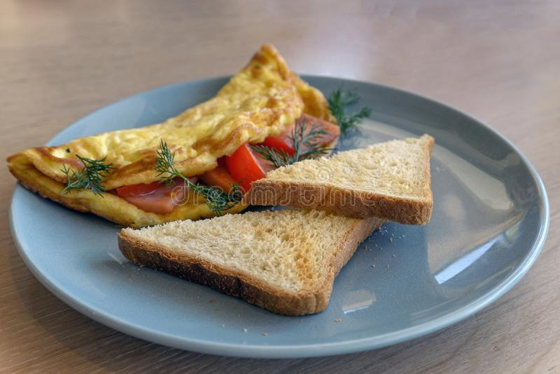 Ovos mexidos do café da manhã com tomate e ervas, dois pães torrados brindados fotografia de stock