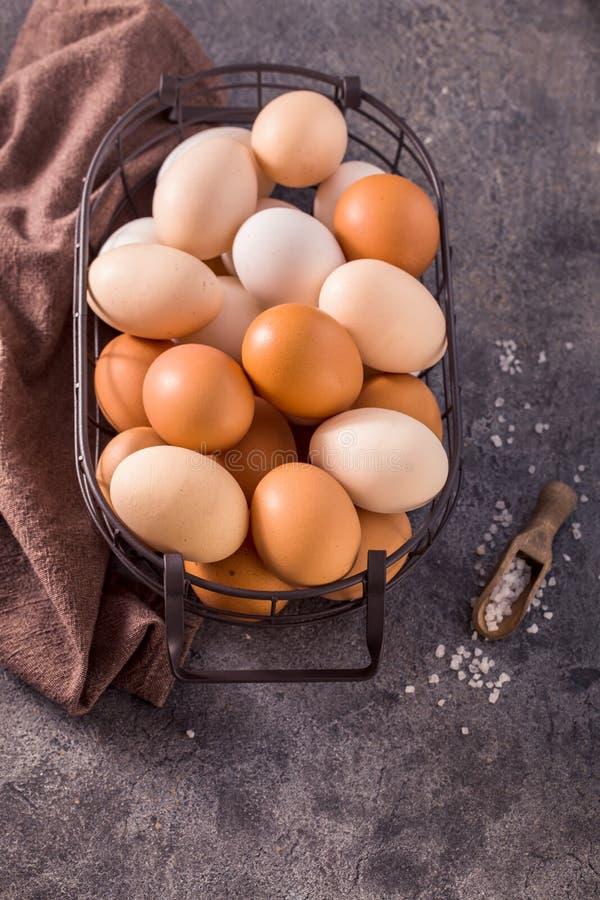 Ovos na cesta de fio no fundo cinzento acima da vista foto de stock
