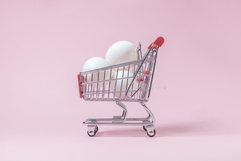 Ovos no carrinho de compras pequeno no fundo do rosa pastel foto de stock royalty free
